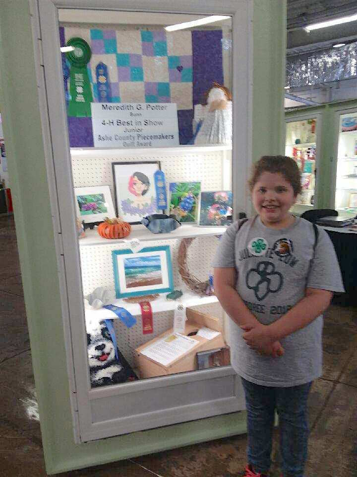 4-Her posing with 1st Place, 4-H Best in Show Junior, and Special Award from the Ashe County Peacemaker Quilt Junior