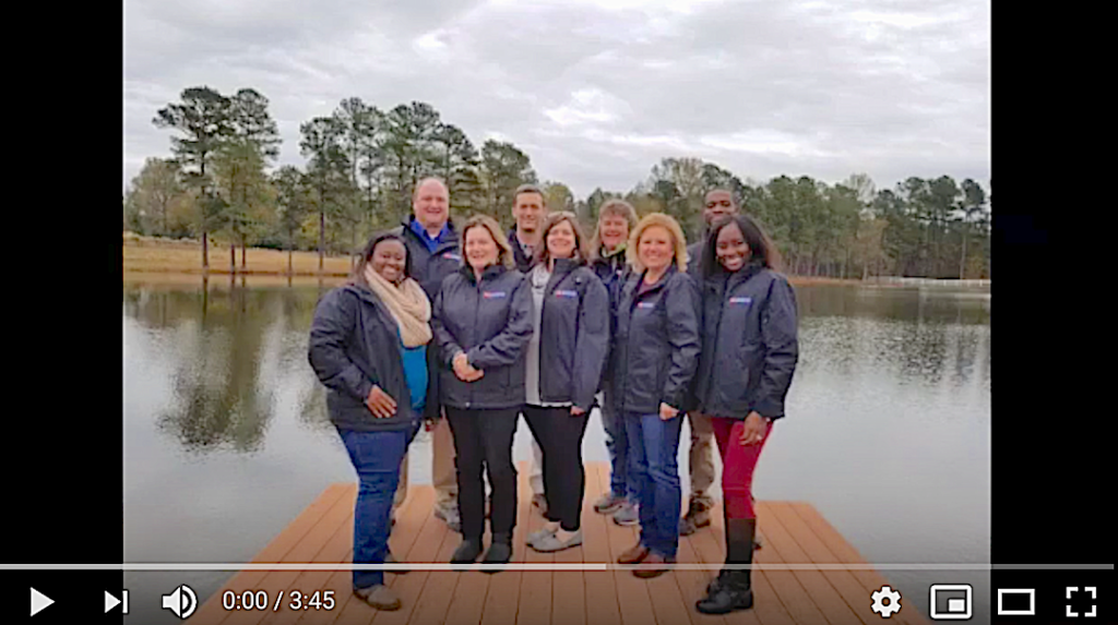 Image of first slide of the 2019 Impacts and Outcomes video with the staff at our retreat on a dock at a lake.