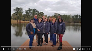 2019 Staff pic standing on a dock in front of a lake
