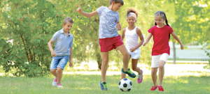 image of four kids playing soccer in a yard.