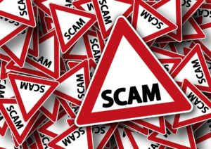 Red and white triangular road sign that says scam