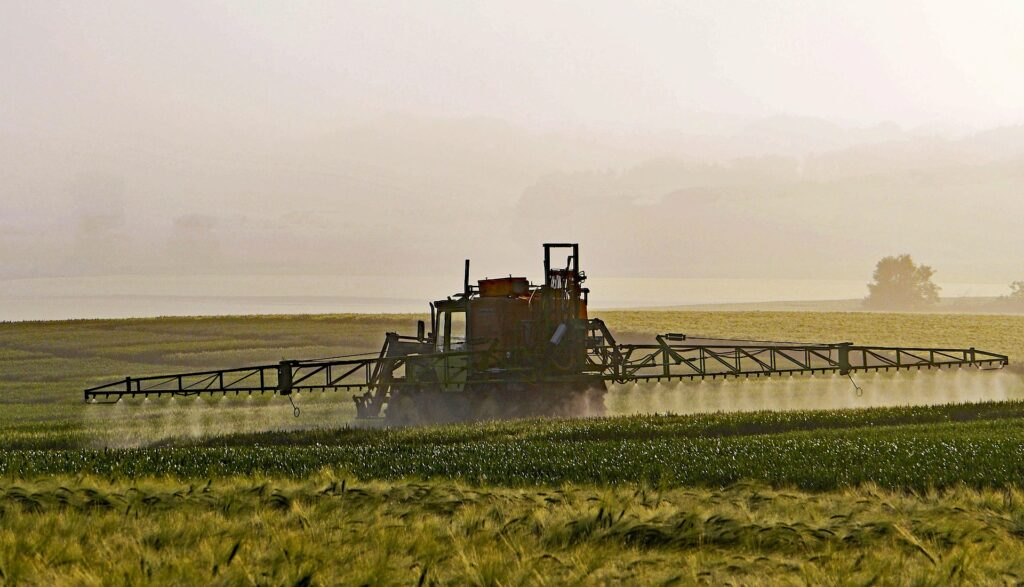 tractor spraying pesticide on field of crops