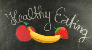 Healthy Eating written on a chalkboard above fruits