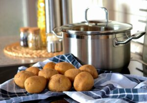 kitchen background, stock pot, potatoes and a dishcloth