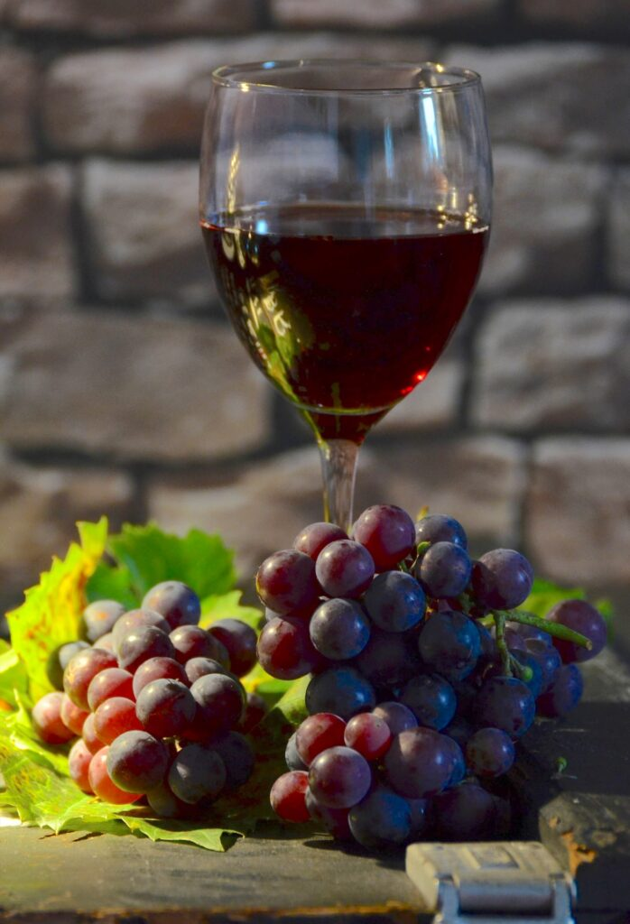 A glass of red wine and s bunch of grapes with leaves on table, brick background